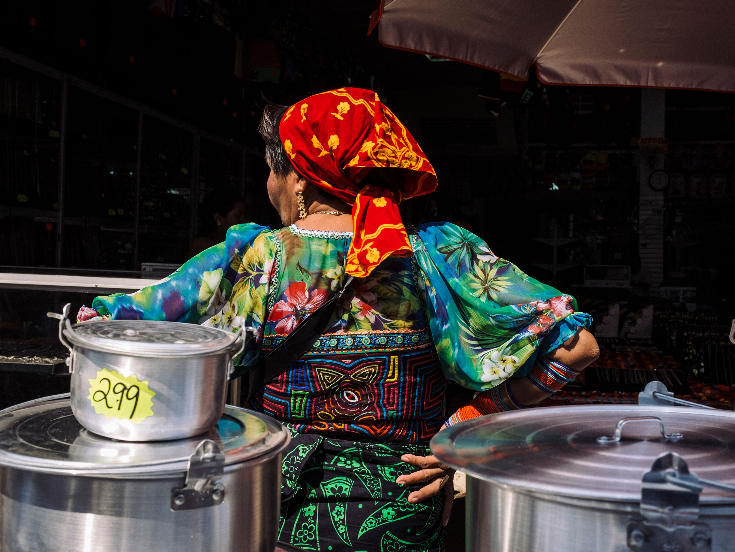 Woman small business owner in Latin American urban marketplace standing in front of market stall