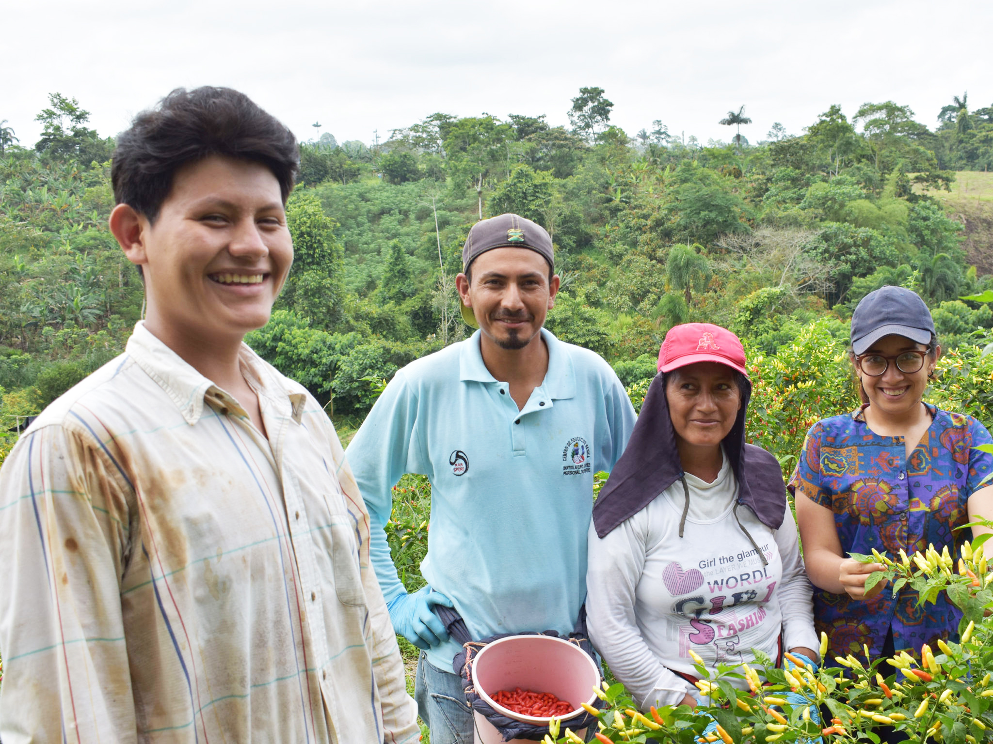 Smallholder farmers and impact investing agronomist smiling in green fields in Latin America